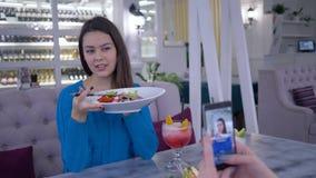 Stående av den vegetariska kvinnan med ny användbar sallad i handen som fotograferas på mobiltelefonen för socialt massmedia unde lager videofilmer