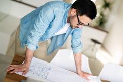 Stående av den vuxna arkitekten som arbetar på plan och ritningar Fotografering för Bildbyråer