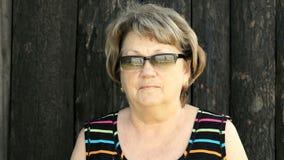 Stående av den vuxna kvinnan i exponeringsglas utomhus stock video