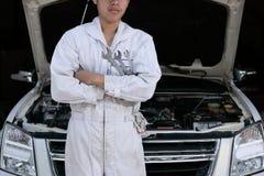 Stående av den yrkesmässiga unga mekanikermannen i enhetlig innehavskiftnyckel mot bilen i öppen huv på reparationsgaraget royaltyfria foton