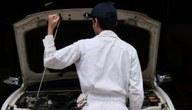 Stående av den yrkesmässiga unga mekanikermannen i likformign som lyfter händer på reparationsgaraget försäkring för bakgrundsbil arkivbild