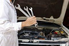 Stående av den yrkesmässiga unga mekanikermannen i vita enhetliga innehavskiftnycklar mot bilen i öppen huv på reparationsgaraget Royaltyfria Bilder
