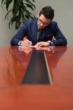 Stående av det attraktiva affärsmanReading Paper In kontoret Arkivfoton