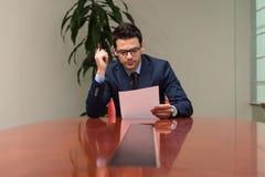 Stående av det attraktiva affärsmanReading Paper In kontoret Arkivbild