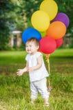 Stående av det gulliga asiatiska barnet med ballonger som applåderar henne händer Royaltyfri Foto