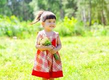 Stående av det gulliga liten flickabarnet som ler med blommor Royaltyfri Bild