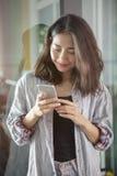 Stående av det härliga asiatiska läs- meddelandet för mer ung kvinna i sma Fotografering för Bildbyråer