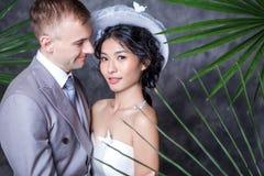 Stående av det härliga brudanseendet med brudgummen mot väggen royaltyfri foto