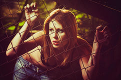 Stående av det härliga ung flickaanseendet bak det metalliska staketet Royaltyfri Bild