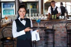 Stående av det hållande portionmagasinet för bartender med exponeringsglas av coctailen royaltyfri bild