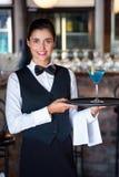Stående av det hållande portionmagasinet för bartender med exponeringsglas av coctailen arkivfoto
