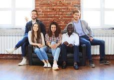 Stående av det idérika affärslaget som tillsammans sitter och skrattar Blandras- affärsfolk tillsammans på starten Arkivfoto