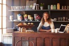 Stående av det kvinnliga anseendet för coffee shopägare bak räknare royaltyfri foto
