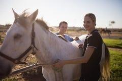 Stående av det kvinnliga jockey- och veterinäranseendet vid hästen fotografering för bildbyråer
