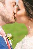 Stående av det kyssande gifta paret på grönt fält Arkivbild