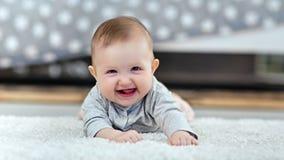 Stående av det lilla le lilla barnet som ligger på fluffig matta som ser kameran i modern inre