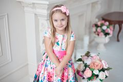 Stående av det lilla le flickabarnet i den färgrika klänningen som inomhus poserar arkivfoton