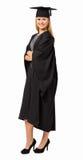 Stående av det lyckliga korset för armar för studentIn Graduation Gown anseende Arkivbilder