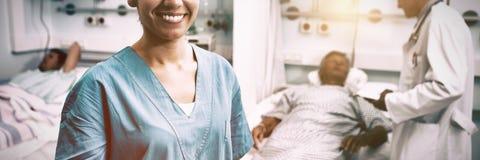 Stående av det lyckliga sjuksköterskaanseendet i sjukhusrum arkivbilder
