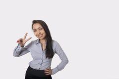 Stående av det lyckliga tecknet för affärskvinnavisningseger mot grå bakgrund royaltyfria foton