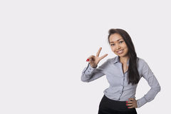 Stående av det lyckliga tecknet för affärskvinnavisningseger mot grå bakgrund arkivfoto