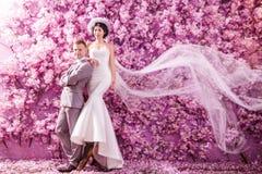 Stående av det säkra bröllopparanseendet mot väggen som täckas med rosa blommor Fotografering för Bildbyråer
