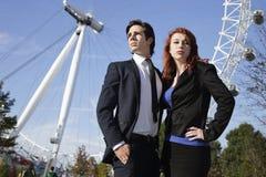 Stående av det säkra unga affärskvinnaanseendet mot det London ögat med kollegan, London, UK Royaltyfria Bilder