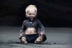 Stående av det smutsiga barnet på den svarta san stranden Fotografering för Bildbyråer