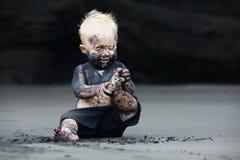 Stående av det smutsiga barnet på den svarta san stranden Royaltyfri Bild
