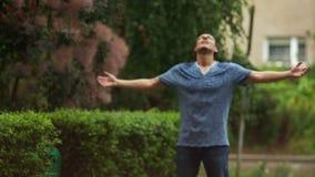 Stående av det stiliga mananseendet i regnet och att lyfta upp hans händer stock video