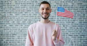Stående av det stolta amerikanska grabbinnehavet som flyger USA-flaggan på bakgrund för tegelstenvägg lager videofilmer