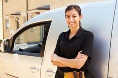 Stående av det unga kvinnliga handelarbetaranseendet vid en skåpbil royaltyfria bilder