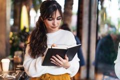 Stående av det unga le kvinnaanseendet i kafé nära fönster som skriver i anteckningsbok Flickan skriver anmärkningsdagboken, gör  royaltyfri bild