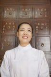 Stående av doktor In Front av medicinkabinettet för traditionell kines arkivfoto