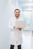 Stående av doktor Holding Laptop, inomhus Arkivfoto