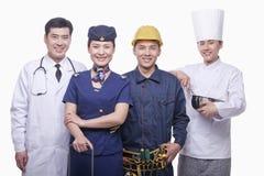 Stående av doktorn, flygvärdinnan, byggnadsarbetaren och kockstudioskottet Royaltyfri Fotografi