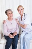Stående av doktors- och patientsammanträde på soffan Royaltyfri Foto