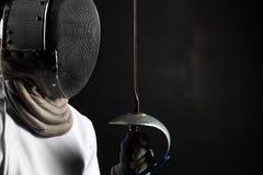 Stående av dräkten för fäktning för fäktarekvinna som den bärande vita öva med svärdet Isolerat på svart bakgrund arkivbilder