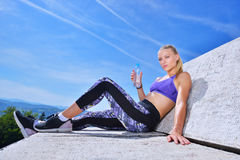 Stående av dricksvatten för ung kvinna, når att ha joggat Royaltyfri Foto