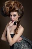 stående av elegant brunhårigt med en stor frisyr Arkivfoton