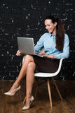 Stående av elegant klätt brunettkvinnasammanträde i vindlägenhet och arbete på den bärbara bärbara datorn arkivfoton