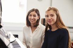 Stående av eleven med kurs för lärarePlaying Piano In musik arkivfoto