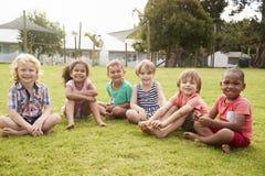 Stående av elever på den Montessori skolan under utomhus- avbrott fotografering för bildbyråer