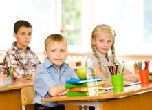 Stående av elever som ser kameran i klassrum Arkivbilder