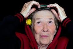 Stående av en äldre kvinna med grått hår som gör hennes hår och dekorerar det med en maskrosblomma royaltyfria bilder