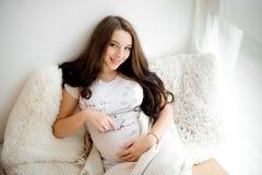 Stående av en älskvärd le långhårig gravid kvinna arkivfoton