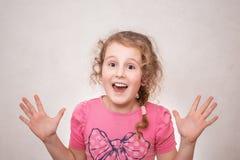 Stående av en älskvärd liten lockig flicka, le som visar tio objekt som isoleras på grå bakgrund arkivbilder