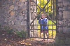 Stående av en årig flicka små fyra på en gammal järnport i en parkera i höst fotografering för bildbyråer