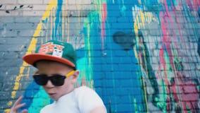 Stående av en 5-årig gatadansare, A kyler 5 åriga barndanser i solglasögon nära en tegelstenvägg med grafitti arkivfilmer