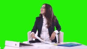 Stående av en affärskvinna Brunetten i exponeringsglas som i regeringsställning sitter, och undertecknande dokument och ler ger d lager videofilmer